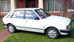 KB Ford Laser with non-factory wheelcovers.